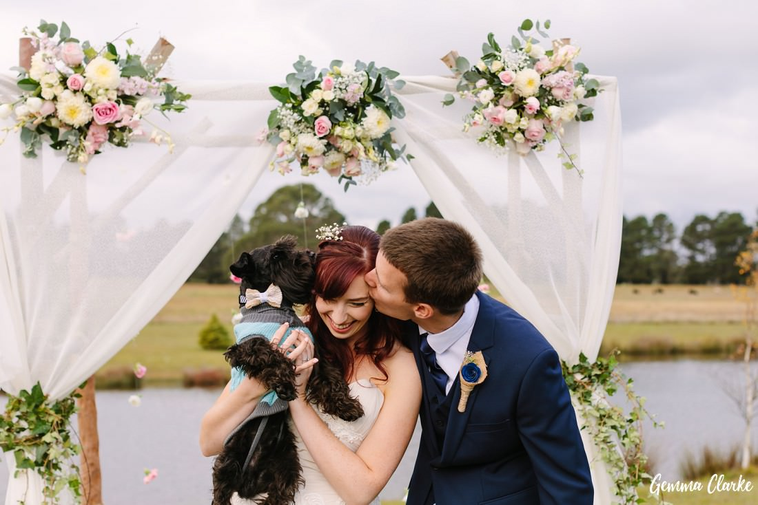 Bride being kissed by the groom and their little dog under the floral decorated arbour at this Autumn Southern Highlands Wedding