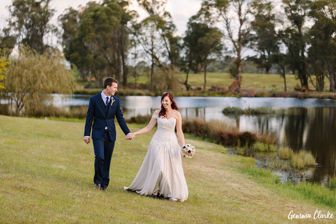 Bride and groom walk hand in hand by the side of the lake and are laughing at this Autumn Southern Highlands Wedding