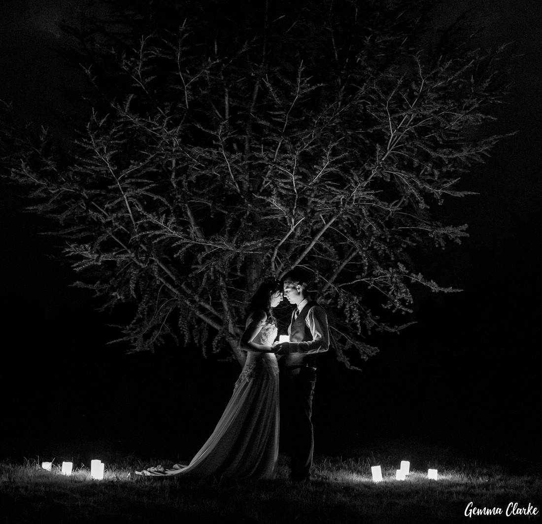 A night scene of the bride and groom standing close to each other holding a candle and surrounded by candles under a lit up tree at this Autumn Southern Highlands Wedding