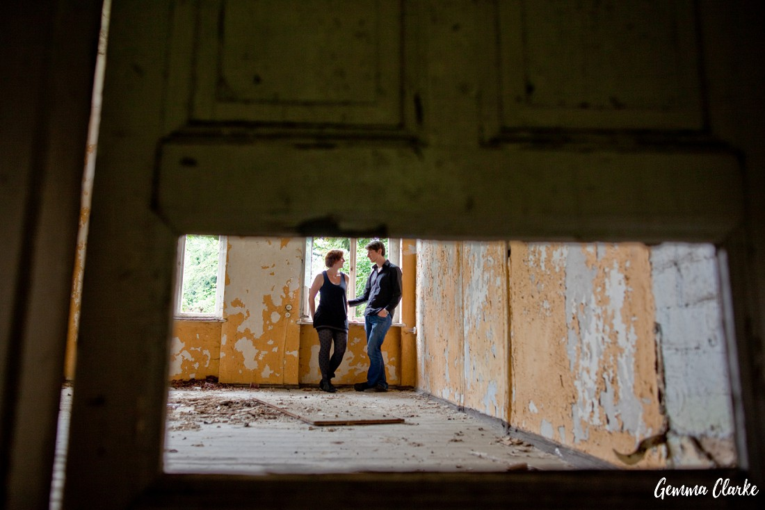 Couple stand together and we see them through a rectangular gap in a door in these Berlin couple portraits