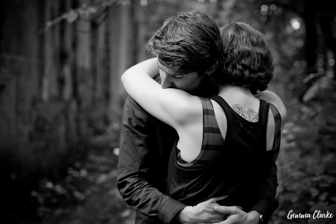 A sweet moment between the couple as they hug in the forest and showing off part of the girl's angel tattoo on her back in these Berlin Couple Portraits