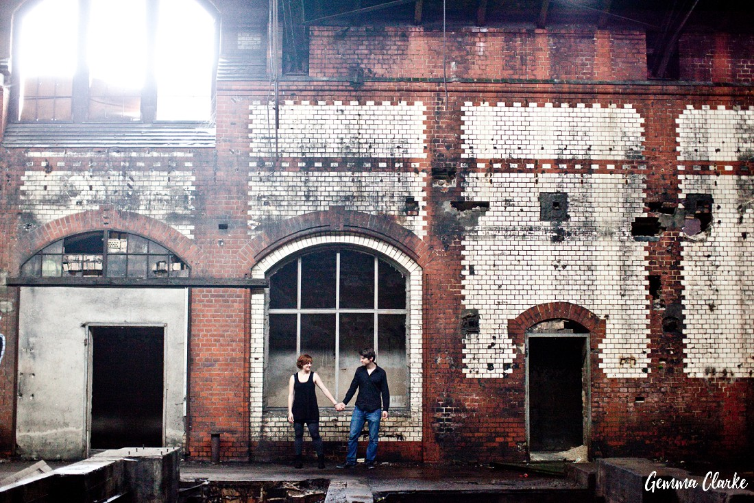 Indoor of a huge open space in an abandoned building and the couple are small and holding hands. Lots of brickwork and sun shining through the top left window in thee berling couple portraits