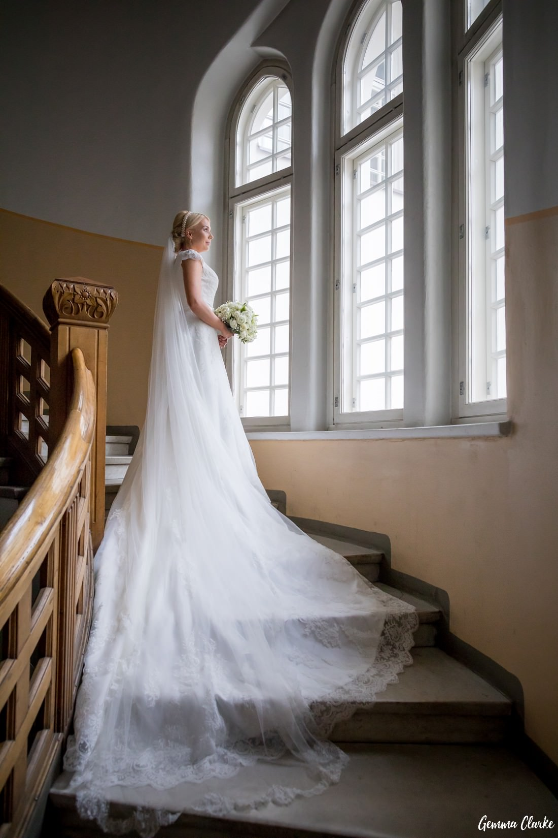 Bride standing on a stairwell with long veil and train falling down the stairs like a waterfall and looking out the large oval window at this Tampere Wedding