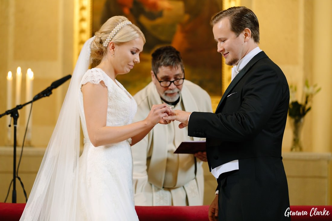 Bride and Groom exchange rings during the wedding ceremony with the groom smiling big at this Tampere Wedding