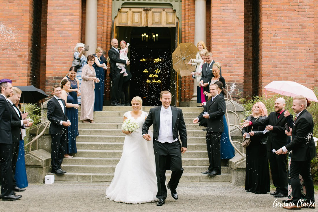Bride and Groom exit the church with their guests throwing rice over them and everyone has a big smile on their face at this Tampere Wedding