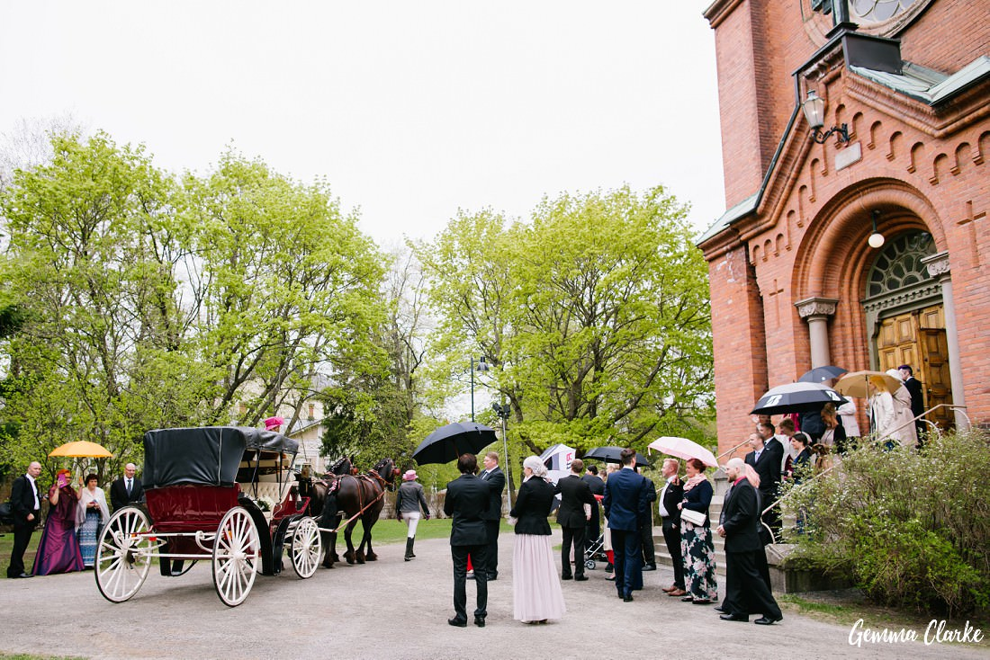 Horse drawn carriage leaves the church as the guests look on at this Tampere Wedding
