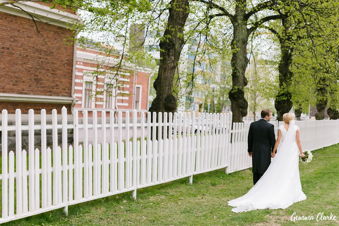 Bride and Groom walk hand in hand alongside a beautiful white fence with overhanging trees at this Tampere Wedding