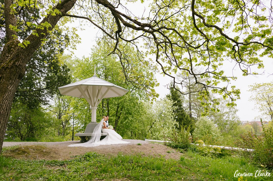Bride and Groom sitting under a gorgeous shelter in very green surroundings at this Tampere Wedding