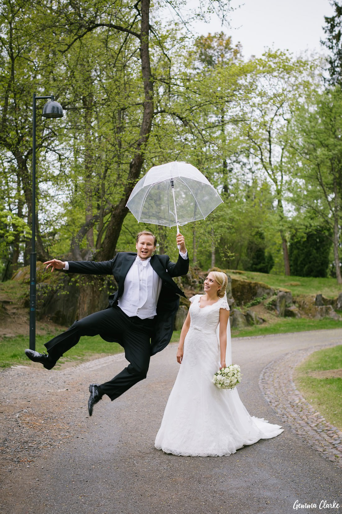 Groom jumps in the air with umbrella as bride watches at this Tampere Wedding