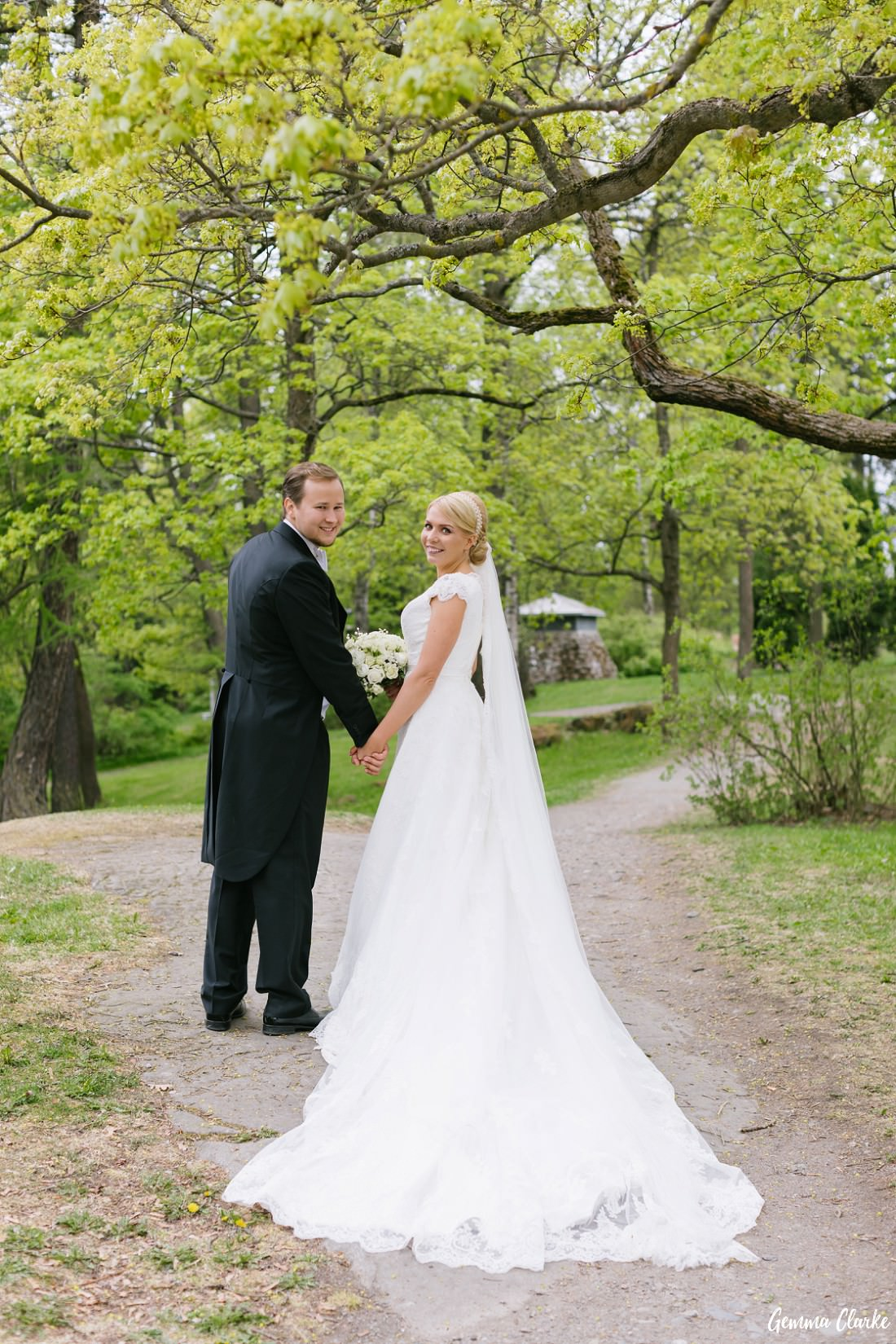 Bride and Groom walking hand in hand and looking back through the gorgeous park at this Tampere Wedding