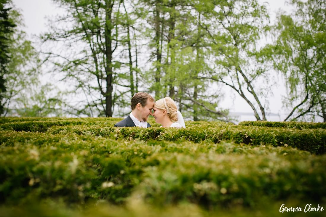 Bride and groom heads pop up from a green garden maze and they look closely at each other at this Tampere Wedding