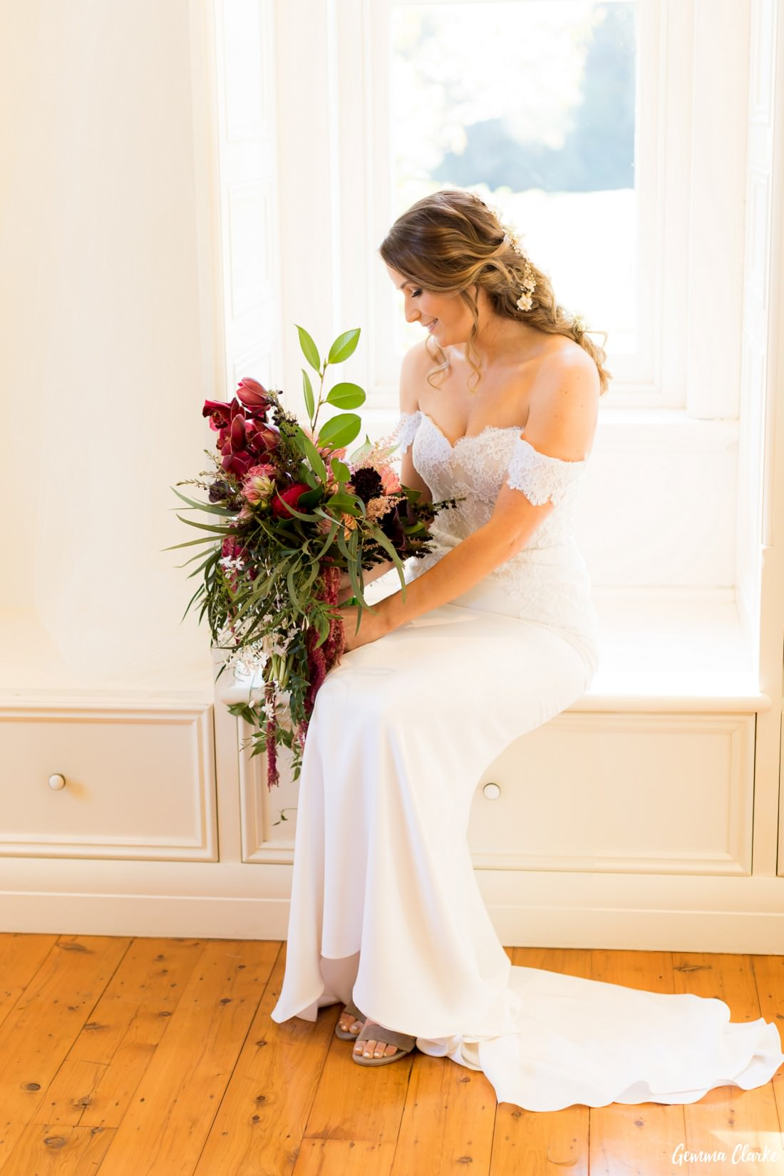Bride dressed in an off the shoulder lace gown with a big bouquet of burgundy flowers sitting down at this Willow Farm Wedding