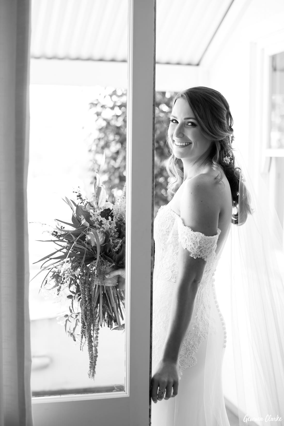 Stunning bridal portrait as she walks outside onto the verandah with her veil trailing behind her at this Willow Farm Wedding