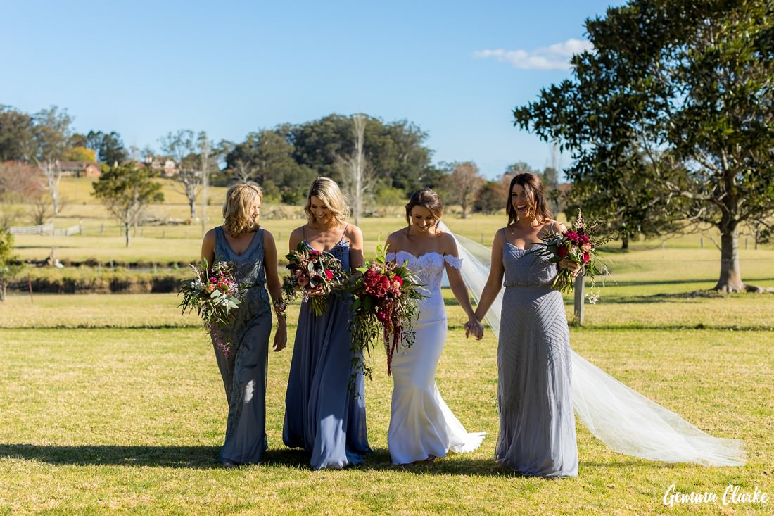 Bridesmaids in stunning silver gowns walking with the bride across country grounds with a dam in the background at this Willow Farm Wedding