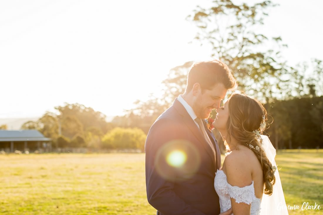 The sun shines down on the couple in love as they snuggle together in wedding attire with a country background at this Willow Farm Wedding