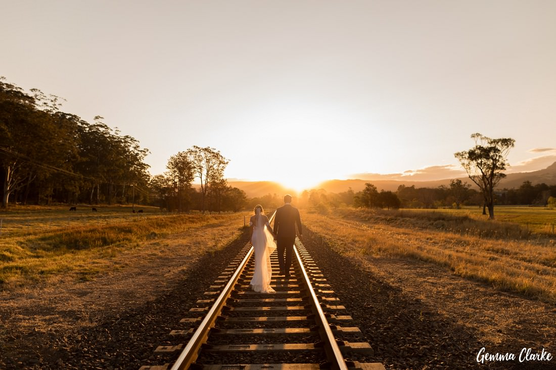 The golden hour is upon us as the bride and groom walk down the middle of the train tracks with the sun shining through them in the distance at this Willow Farm Wedding