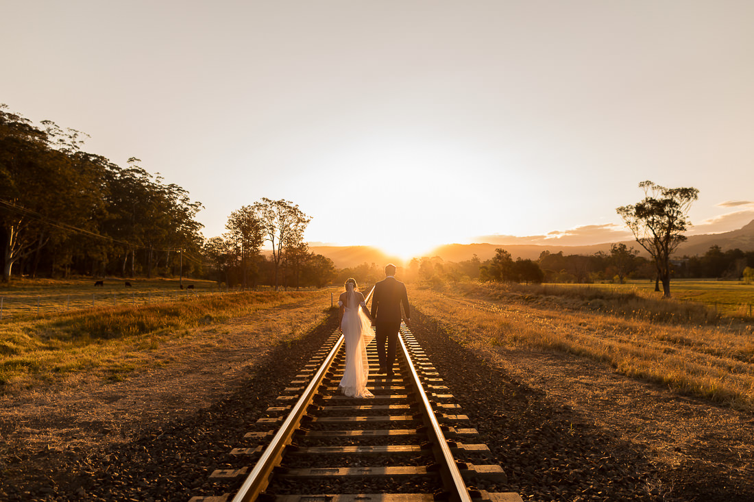 Willow Farm Wedding Sunset bride and groom on train tracks
