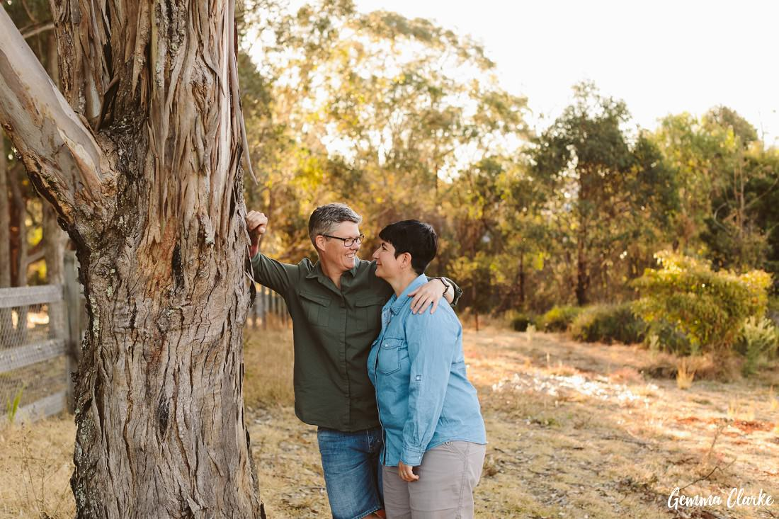 Female couple stand by a lovely old tree as they gaze into each other's eyes at this same sex couple portraits session
