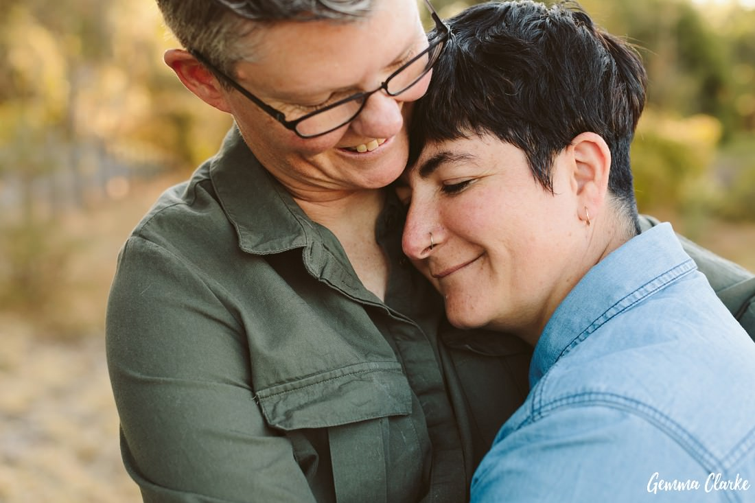 close up of a female couple cuddling and looking very happy at this same sex couple portraits session