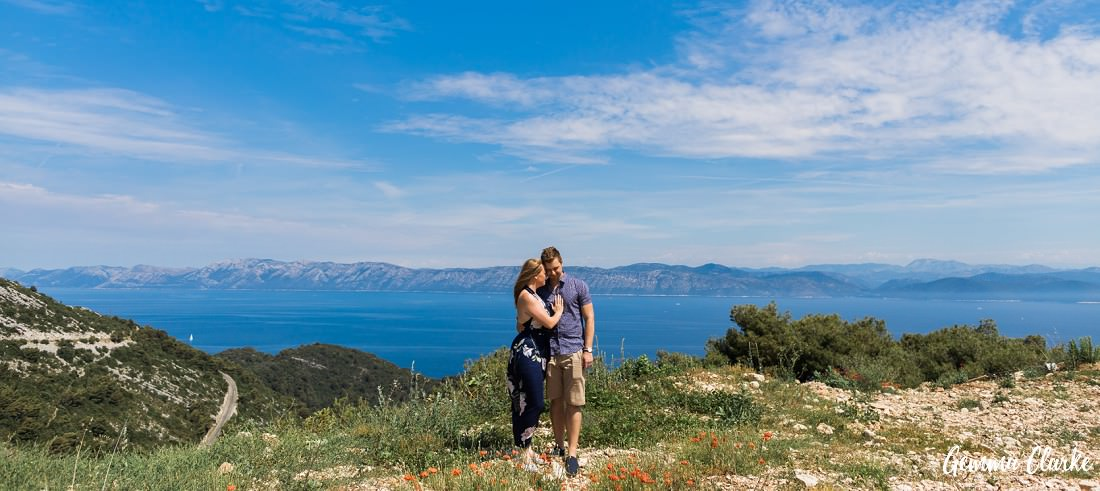 A couple stand in blue clothes on a hill top overlooking the Adriatic Sea in these Portraits on a Croatian Island