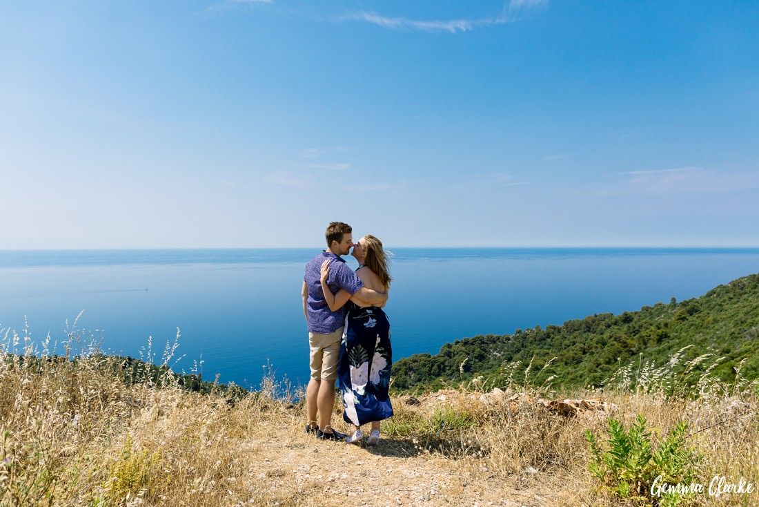 Couple stand arm and arm on a cliff overlooking the amazing Adriatic Sea in these Portraits on a Croatian Island