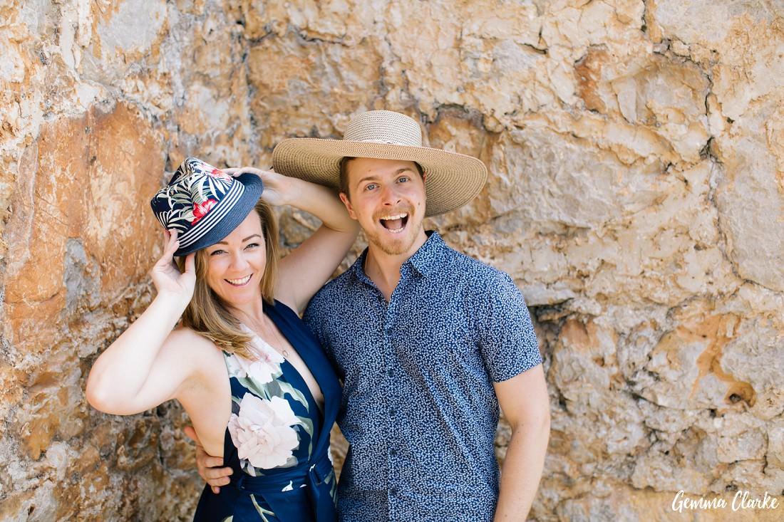 A portrait of a couple wearing each other's hat with happy smiles in front of a stone wall in these Portraits on a Croatian Island