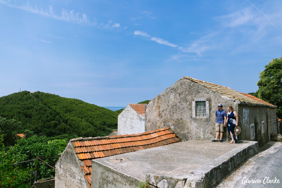 Couple stand next to a very old house overlooking the forest and sea in these Portraits on a Croatian Island
