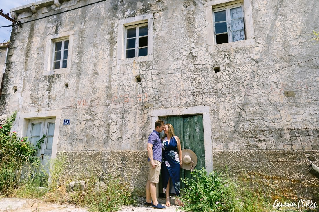 Couple stand in front of a very old house with cracking walls in their summer attire in these Portraits on a Croatian Island