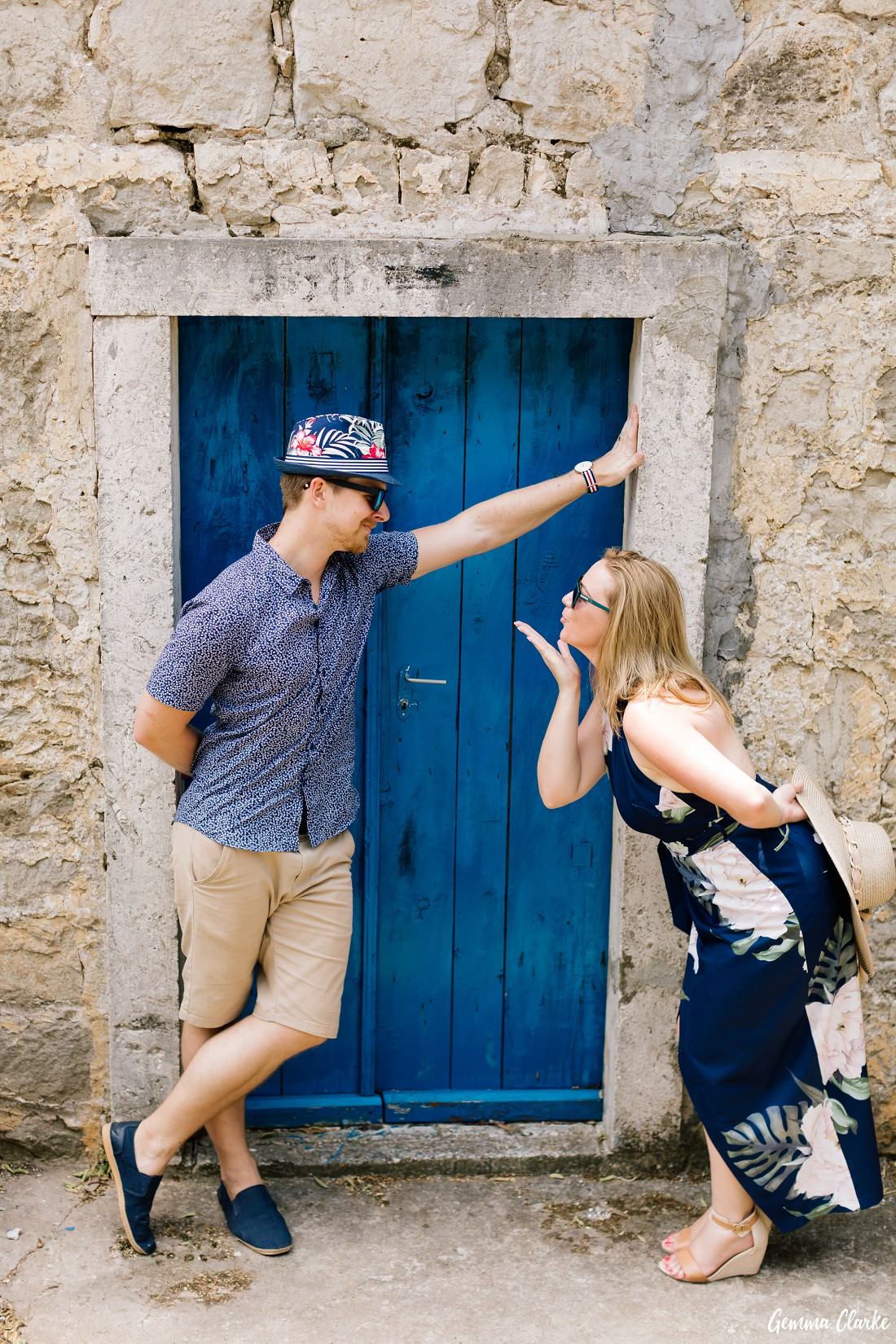 This couple love to pose and they do so in front of a bright blue door as she blows a kiss to him in these Portraits on a Croatian Island