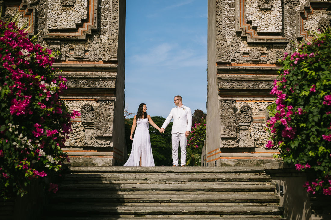 Couple stand holding hands in wedding attire in the opening of a Hindu Temple at the top of the steps at this three minute wedding photo shoot