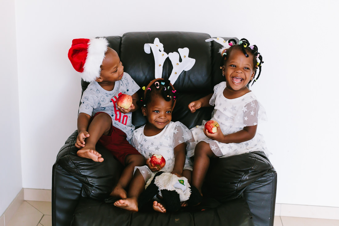 Christmas morning with Triplets from Ghana sit on an armchair with christmas attire including a santa hat and reindeer antlers