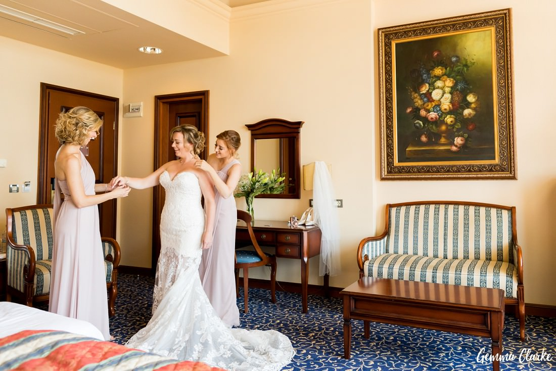 Bride is helped in to her lace wedding gown with two bridesmaids in blush colour dresses in a gorgeous Grand Villa Argentina hotel room at this Dubrovnik Destination Wedding