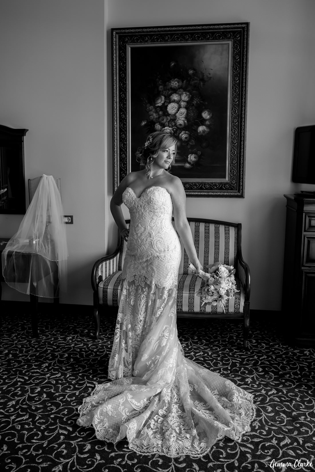 Stunning portrait of bride standing with lace wedding dress train spread out in front of her while standing in front of a large painting at this Dubrovnik Destination Wedding