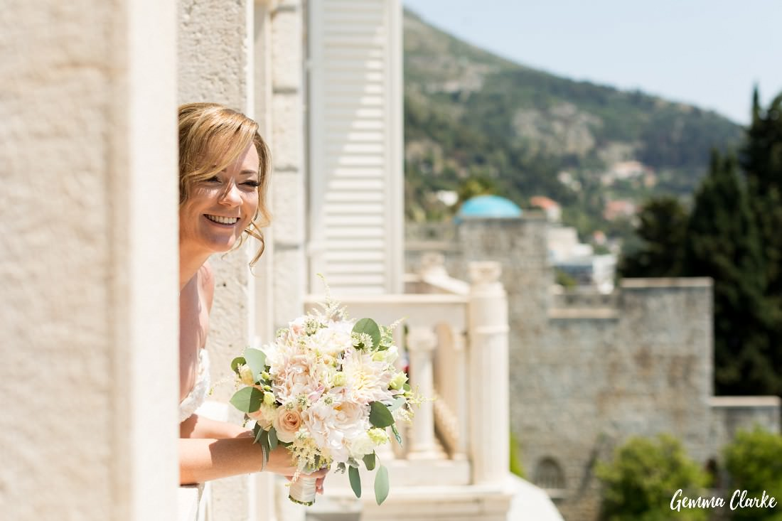 Bride with a big smile on her face while holding her floral bouquet and leaning over the Grand Villa Argentina balcony at this Dubrovnik Destination Wedding