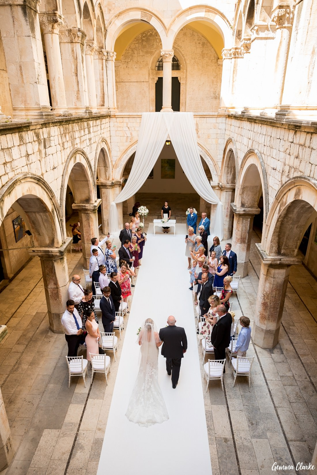 An above angle of the guests in the Sponza Palace watching the bride and her father walk down the aisle at this Dubrovnik Destination Wedding