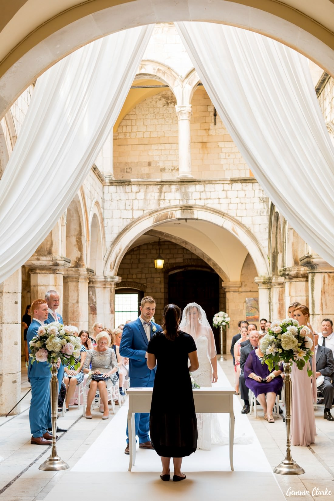 Bride and Groom stand at the end of the aisle in front of the celebrant with a beautiful styled arch and flower stands at this Dubrovnik Destination Wedding