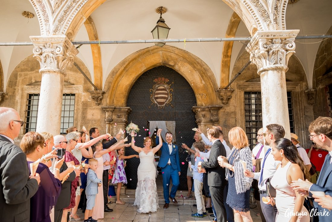Confetti is thrown over the couple as they exit with their hands in the air in front of Sponza Palace at this Dubrovnik Destination Wedding