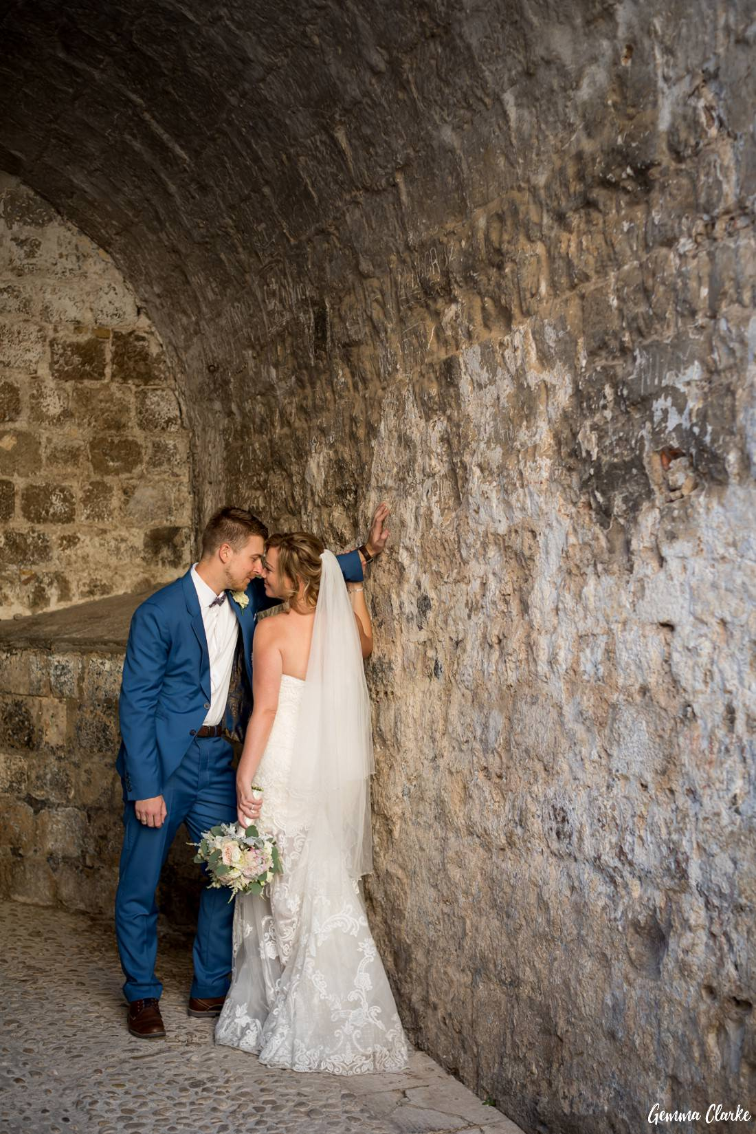 Bride and groom cuddle in the corner of an alley way arch at this Dubrovnik Destination Wedding