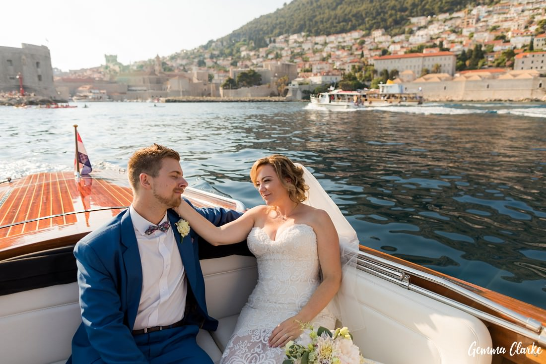 Bride and Groom hold each other as they sit at the back of a wooden boat and the Old Town in the background at this Dubrovnik Destination Wedding