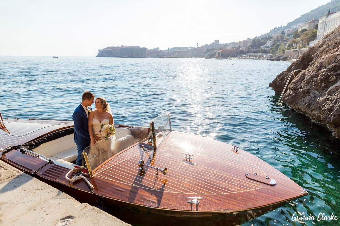 Bride and Groom stand up in a classy wooden boat with the Old Town in the background with the sun shining on them at this Dubrovnik Destination Wedding
