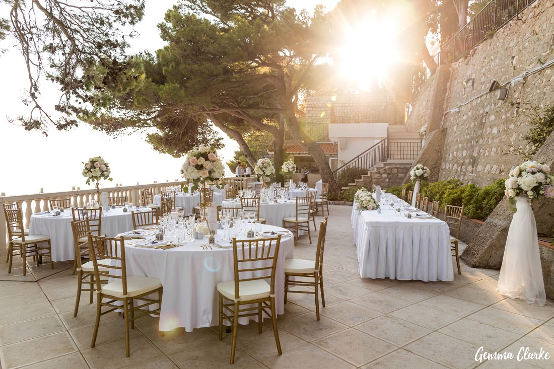 The sun shines on the beautiful styling of the dinner terrace with pastel florals and white tablecloths at this Dubrovnik Destination Wedding
