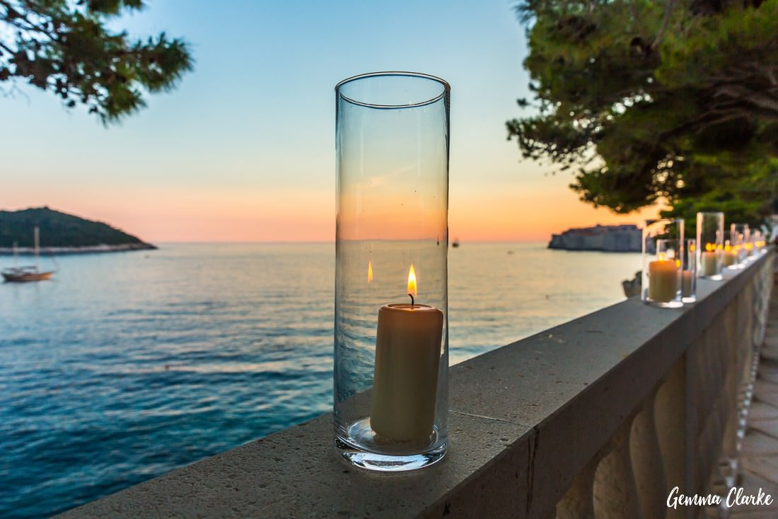 Candle lit along the line of the terrace with other candles and the sun setting in the distance at this Dubrovnik Destination Wedding