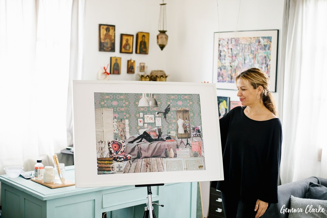 Athina the artist stands by her big collage on an easel in her studio in these Artist portraits in Skopelos Greece