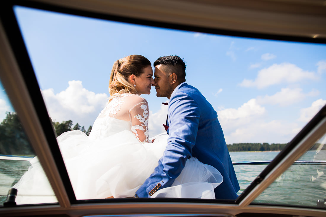 Bride and Groom sit on the front of a speedboat on the water on a sunny day at this Porvoo Wedding in Finland