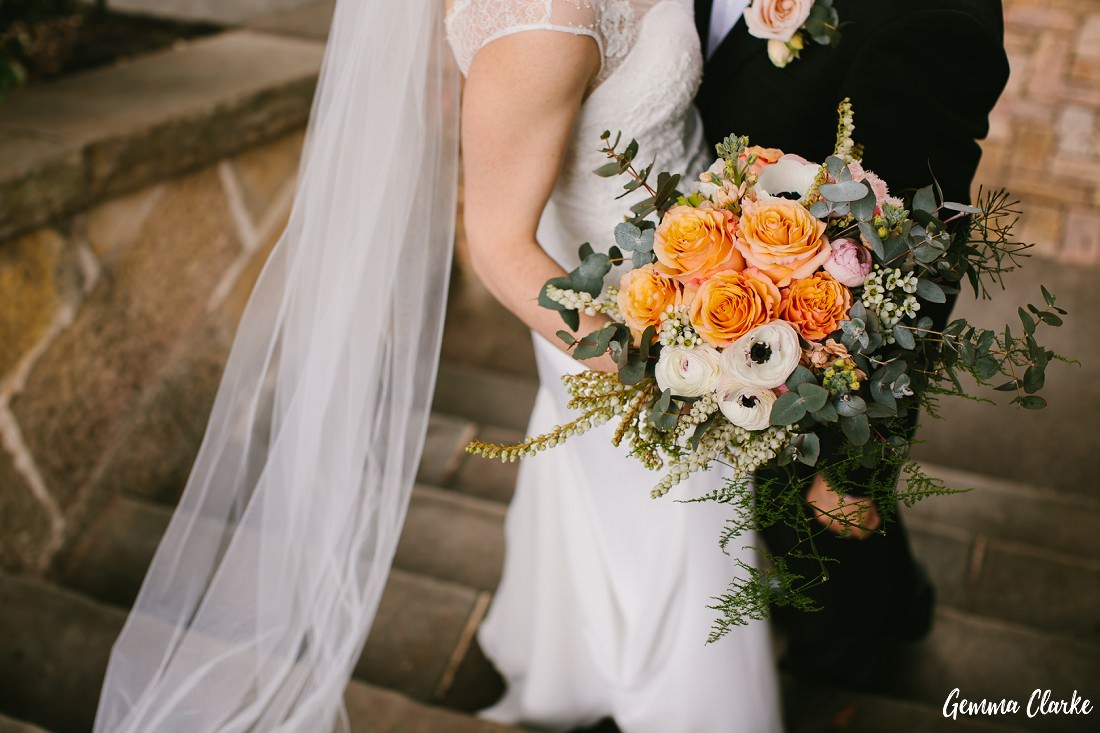 Stunning flowers by Pearson's florist with pastel colour and a brighter apricot colour while the bride and groom cuddle at this small wedding Sydney.