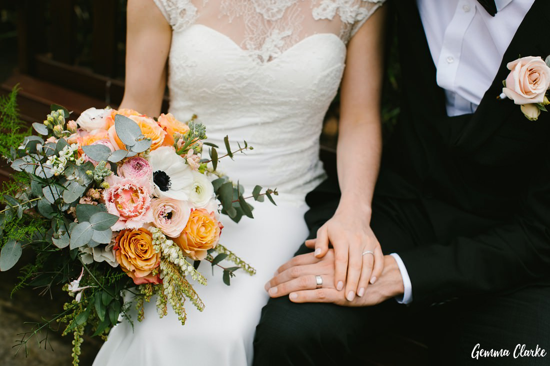 Bride and groom seated showing off their wedding bands with a big bouquet of pastel coloured flowers at this small wedding sydney