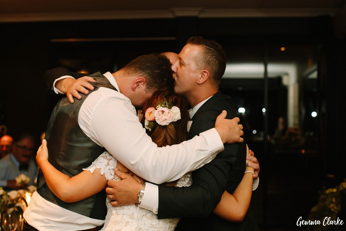 Big group hug after an emotional family speech at this Stanwell Tops wedding