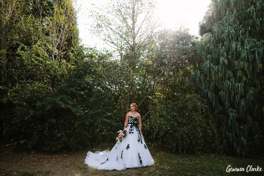Bride poses in front of the forest before getting ready to walk down the aisle at this Briars Country Lodge Wedding