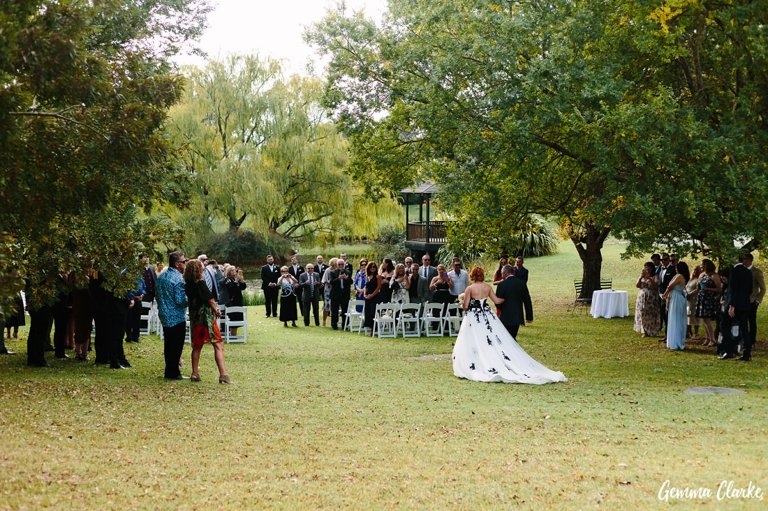 The bride walks toward the aisle across the grass as all her guests look on at this Briars Country Lodge Wedding