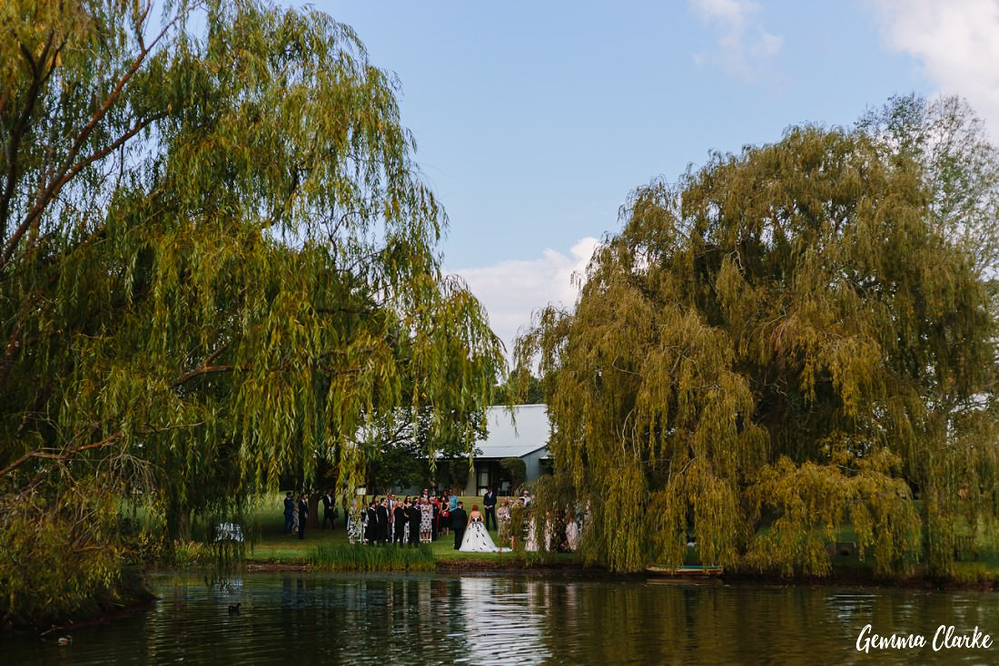A view across the water to the wedding ceremony at this Briars Country Lodge Wedding